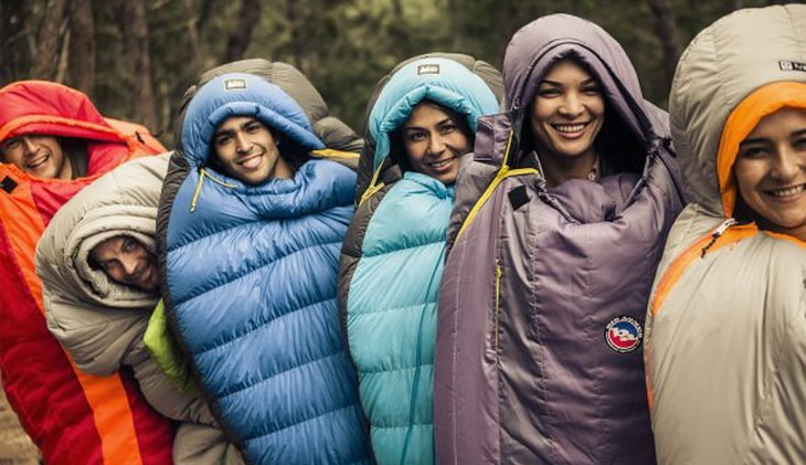 Group of people in sleeping bags taking a picture