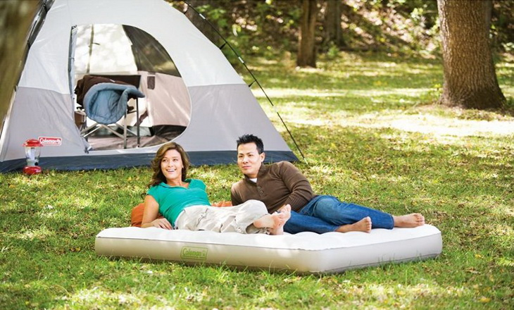 Two adults sitting outside on the most comfortable camping bed
