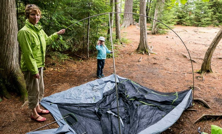 A mother and a child setting up a tent