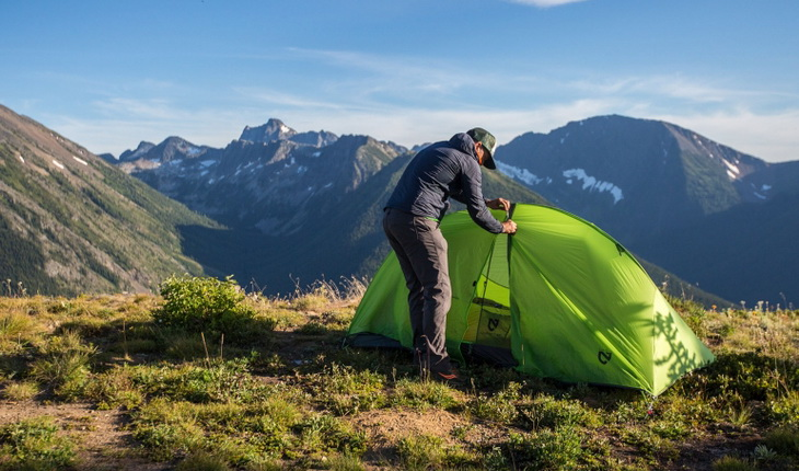 A man setting up the Nemo Hornet 2P tent in the mountains