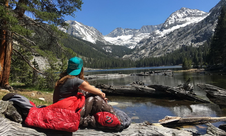 Woman in a Nemo sleeping bag looking at the mountain landscape