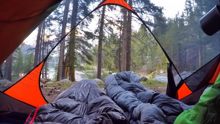 Two adults in Nemo sleeping bags looking at a lake