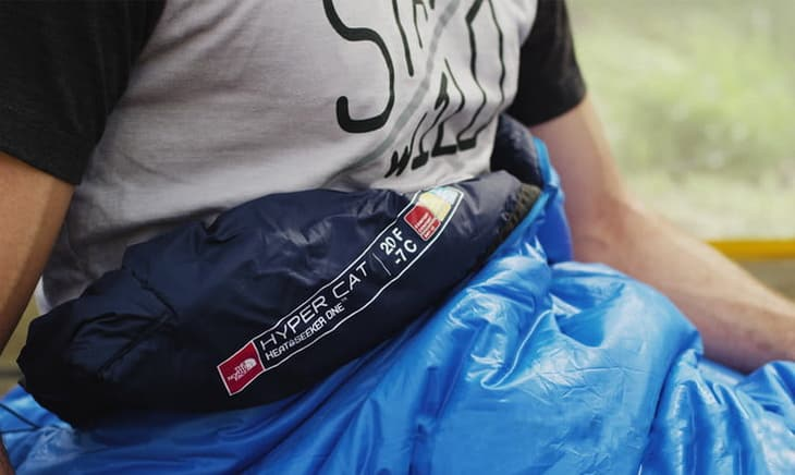 A man in the North Face HyperCat 20, which is crafted with a durable and lightweight synthetic insulation