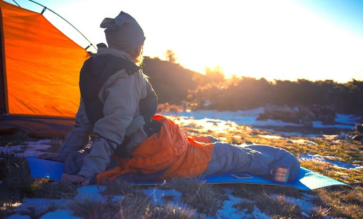 Girl sitting in a sleeping bag and watching the landscape in the morning