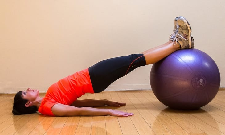 Woman performing Stability Ball Glute Bridge Exercise