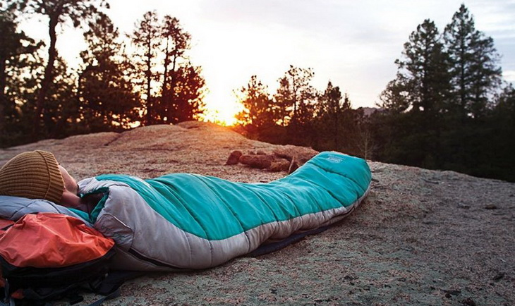 The man is lying in a sleeping bag