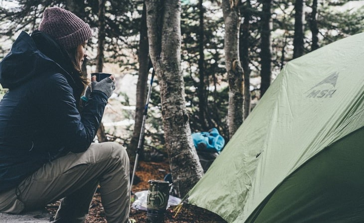 Woman near a tent driking hot coffee in the morning