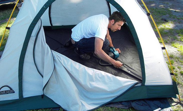 A man cleaning a tent