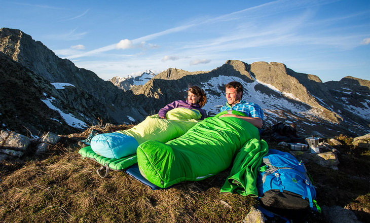 Two adults sitting in sleeping bags outside in the nature
