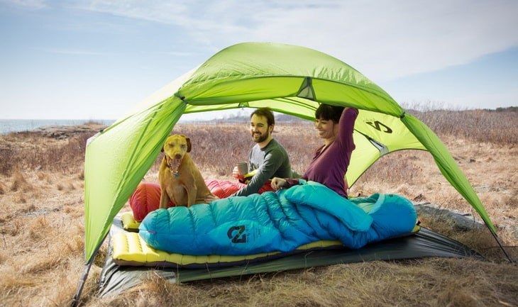 A couple camping in the wilderness with their dog