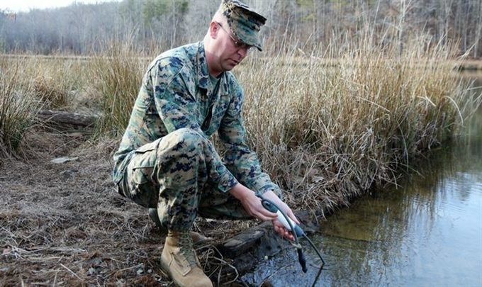 A man using a water filter in a pond