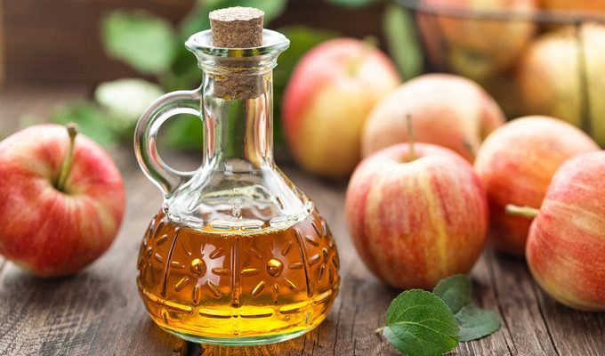 Apple Cider Vinegar and few apples on the table