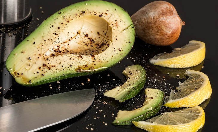 Half of avocado and few slices of lemon on the table