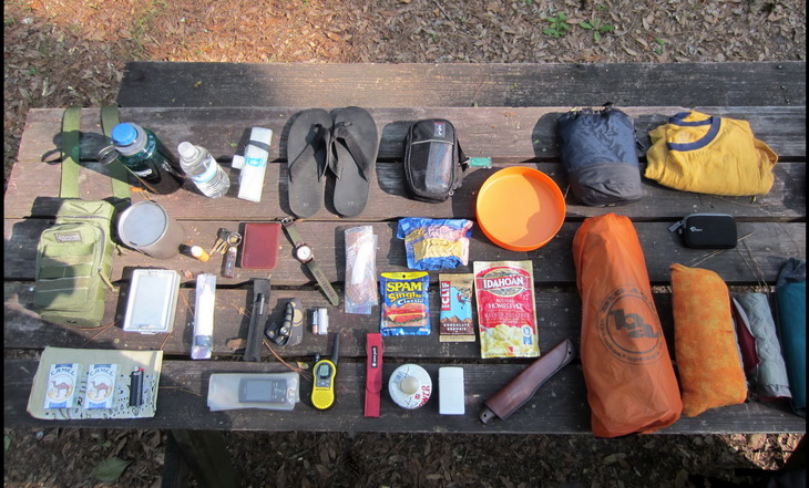 backpacking gear on a wooden table outside