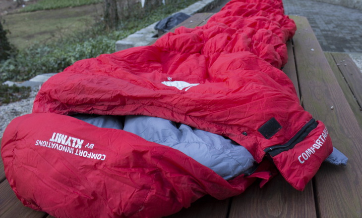 Man in Klymit KSB 20 Sleeping Bag laying on a table outside