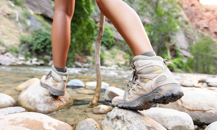 Woman passing the river wearing hiking boots