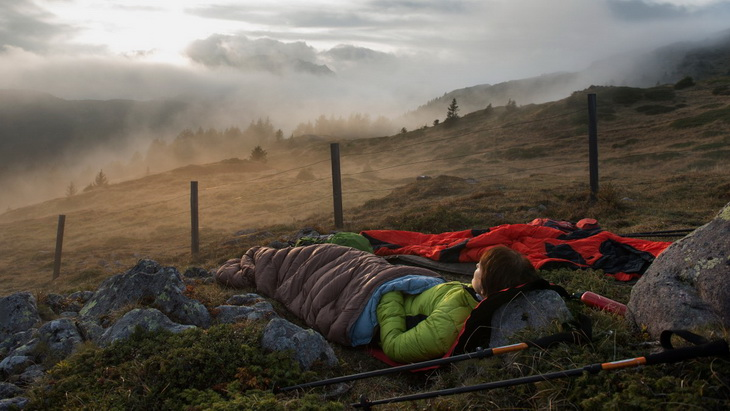 woman in a sleeping bag watching the sunset