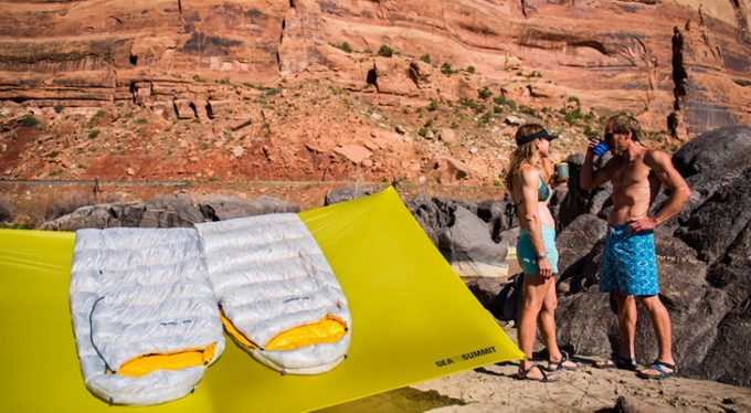 A couple and two Sea to Summit Spark SP III sleeping bags laying on tent in the sun