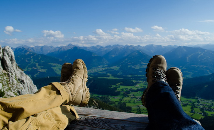 two persons laying on the ground and watching the view