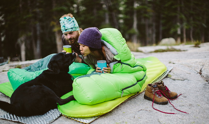 A couple in sleeping bags sitting outside with their dog