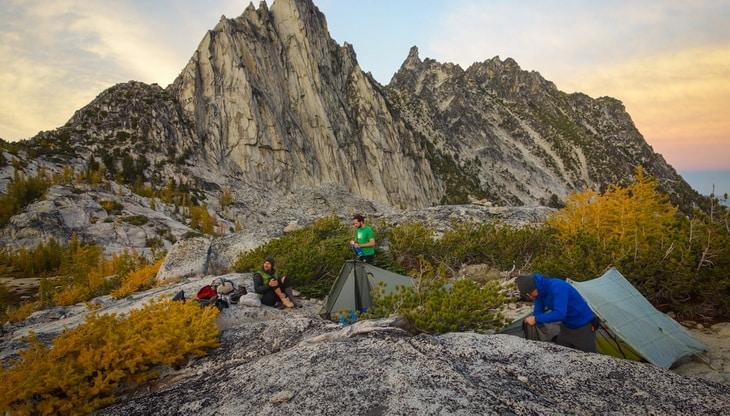 Three hikers near tents