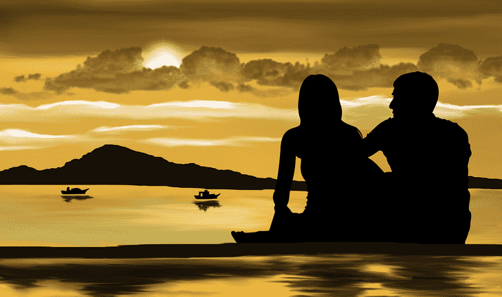 a couple on a beach at sunset