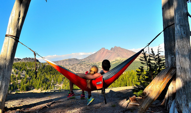 Couple relaxing in Eagles Nest Outfitters DoubleNest hammock and looking at the mountain