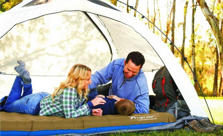 family-relaxing-in-the-tent sitting on a camping bed