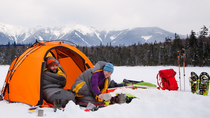 Two adults in Nemo Sonic Down Sleeping Bags camping in the winter