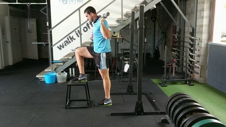 Man practicing high box step up exercise