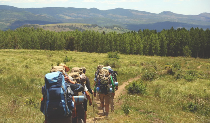 backpackers on a mountain trail in the daytime