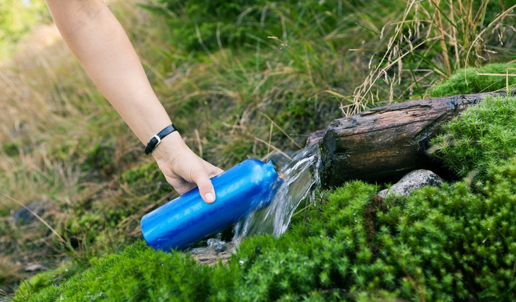 person taking water in a water bottle