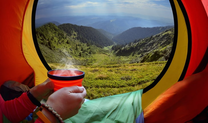 Woman lying in a tent with coffee ,view of mountains and sky in Carpathians mountains, Ukraine,