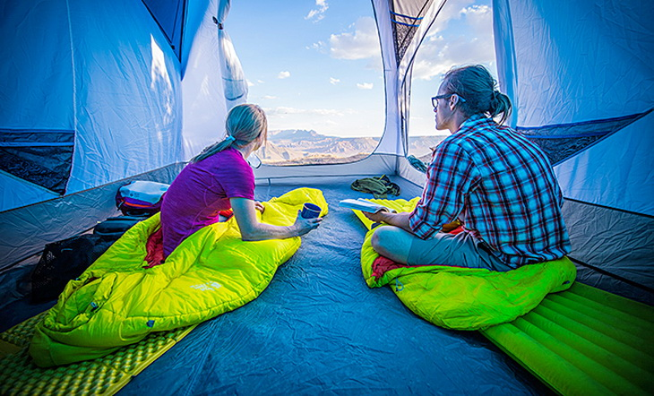 Two adults in Mountain Hardwear HyperLamina Spark 35 Sleeping Bags looking at the landscape