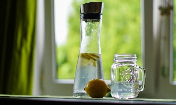 Shallow Focus Photography of Yellow Lemon Near Glass Mason Jar and Glass Decanter
