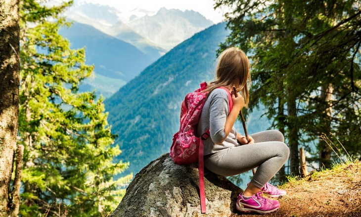 little-girl-hiking-and-resting-on-a-rock