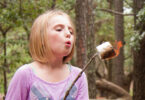 little girl cooking campfire dessert