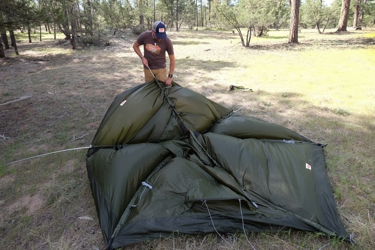 man drying his tent of condensation or moisture