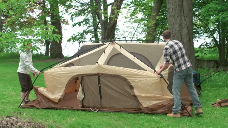 Two persons setting up a tent in the forest