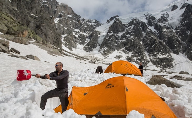 Man moving the snow near a tent