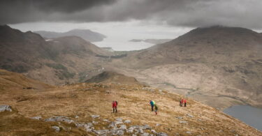 People Standing on Brown Mountain Near Lake Under Gray Clouds during Day Time