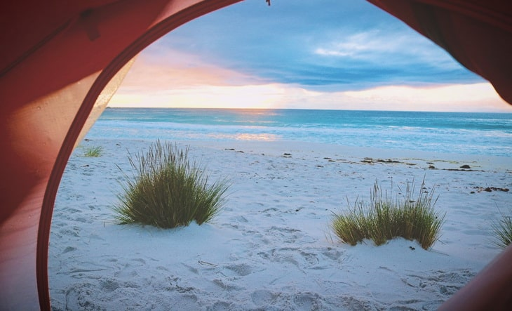 Person Inside Tent Watching Shore Line View during Sunset