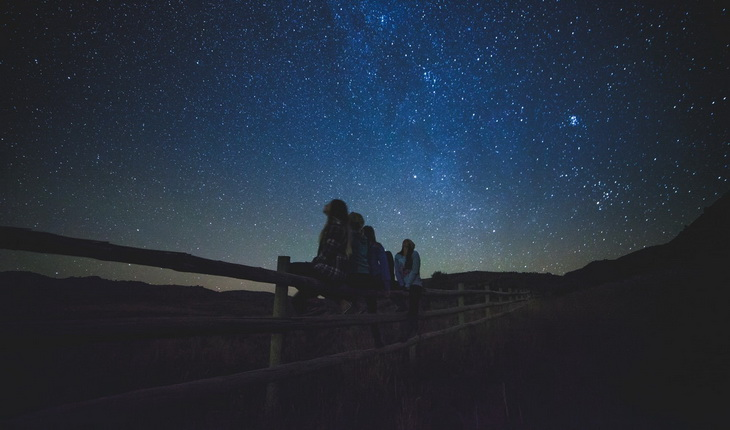Group of People Sitting on Wooden Farm Fences Star Gazing
