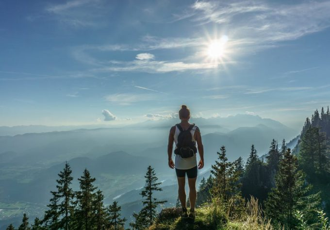 A hiker on the top of a mountain under the sun