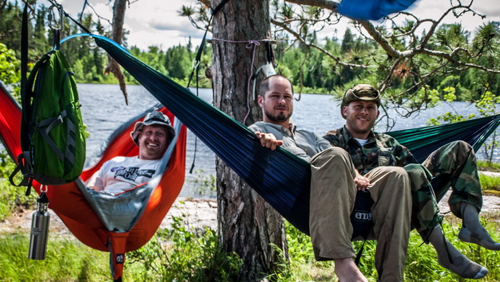 3 adults sitting in Eagles Nest Outfitters DoubleNest hammock outside in the wild