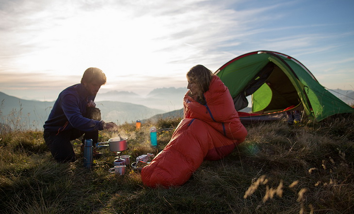 Two hikers on the mountains preparing cofee in the morning