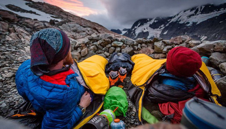 Two adults sitting in sleeping bags looking at the moutains