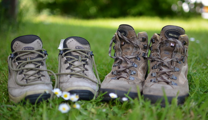 Two pairs of hiking boots on the grass
