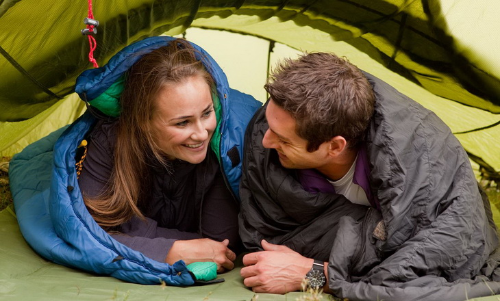 Two adults sitting in sleeping bags in a tent