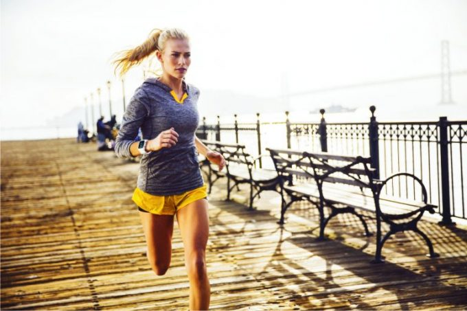 Girl running with a heart rate monitor